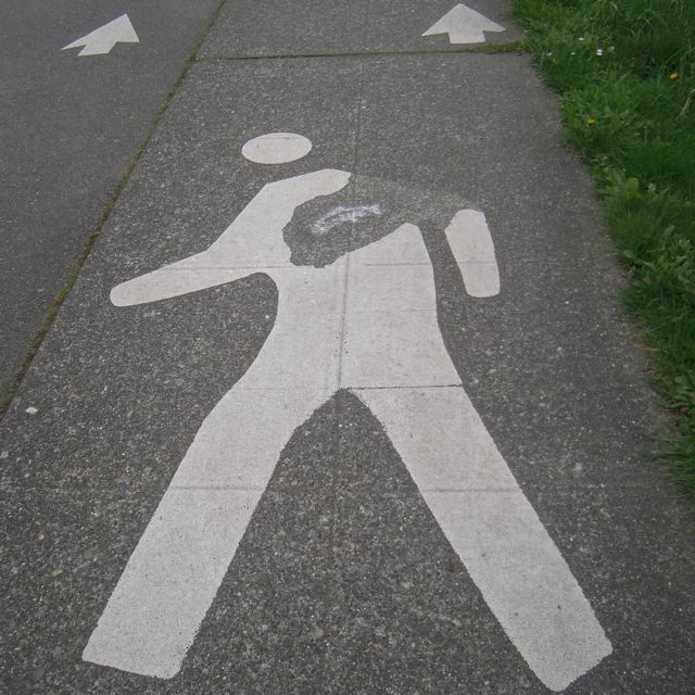 [Worn-away part of a pedestrian logo in the roadway has been stenciled with a leaping fish]