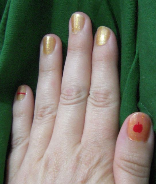 [Red apple with peach-orange background on thumb, other fingers sparkly yellow, red band on little finger]