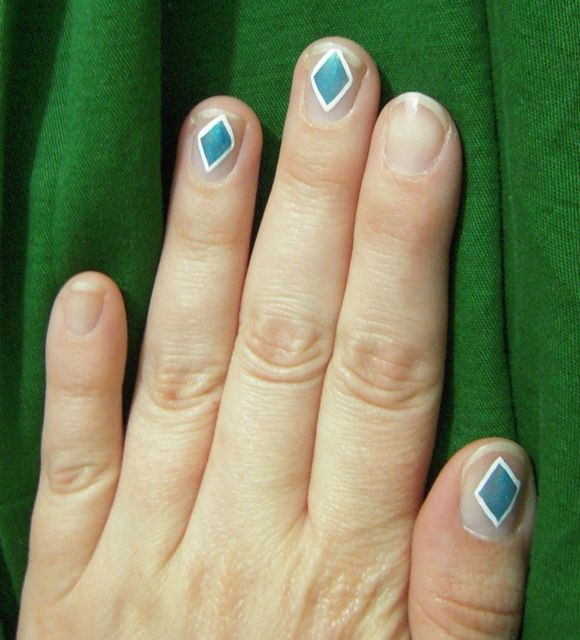 [Three shimmery turquoise diamond shapes outlined in white on natural nails, thumb, middle, and ring fingers]